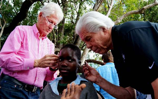 President Bill Clinton and Bill Austin, founder of the Starkey Hearing Foundation, fit a patient with hearing aids at a mission in Zambia in August 2013 (Photo: Starkey Hearing Foundation)