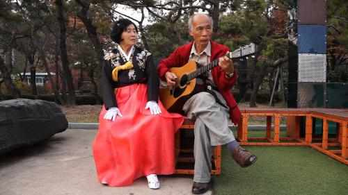 A scene from the movie. An old lady is singing a song in accordance with guitar playing.