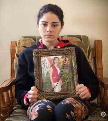 Silvana holds a picture of her sister, Sandi, who was killed by an ISIS bomb while riding the bus to university. Threatened with death by ISIS, Silvana is now in hiding.
