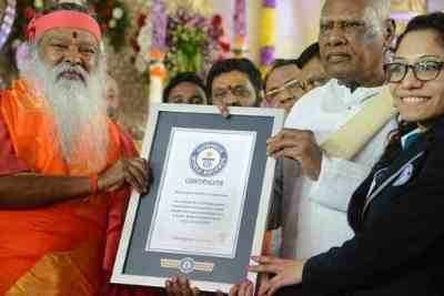 (From left to right) Ganapathy Sachchidananda along with the Governor of the State of Tamilnadu, India accepting the Guinness certificate from Guinness World Record Representative, Ms. Fortuna Burke.
