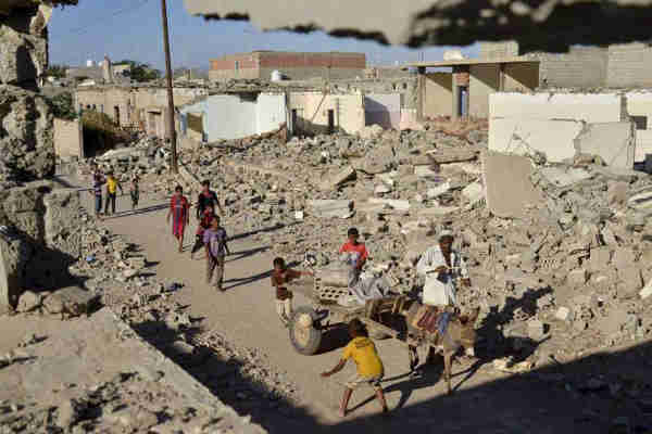 Children play as a donkey cart passes destroyed buildings in the Al-Ora's neighbourhood of Zinjibar, Yemen. Photo: UNHCR / A. Al-Sharif