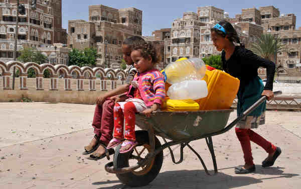 A girl pushes two younger children in a wheelbarrow that also bears several jerrycans in Sana'a, the capital of Yemen. Photo: UNICEF / Mohamed Yasin