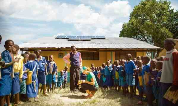 SolarCity photovoltaic designer Alex Webster explains solar energy to students at Kulumbeni Primary School in Matate, Kenya.