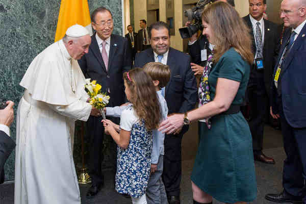 Pope Francis is welcomed by Secretary-General Ban Ki-moon and receives flower bouquets from children of UN staff members at the start of his visit to UN Headquarters. UN Photo / Mark Garten