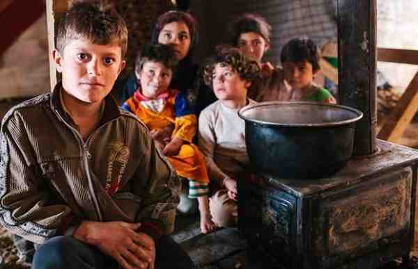 Syria refugees Adel and his siblings try to keep warm by the fire inside their makeshift home in the Bekaa Valley, Lebanon