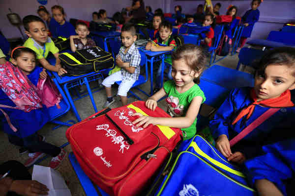 On 13 September 2015 in Syria, 6-year-old Fatima, in Grade 1, smiles after receiving her new schoolbag, on her first day at Nazem Atrash Primary School in Homs City. Photo credit: UNICEF / Sanadiki