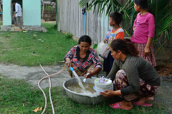 Women wash dishes in Kraing Serey village, Kampong Speu province, Cambodia. Photo: UNDP Cambodia / Chansok La