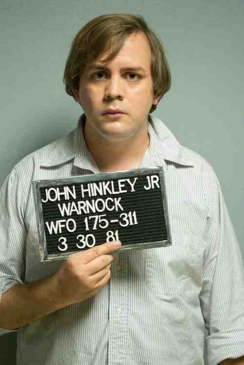 Kyle More portraying John Hinckley Jr after his attempted Presidential assassination.