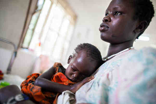 A mother holds her severely malnourished 22-month-old baby in the Al Sabah children's hospital in Juba, South Sudan, while awaiting treatment at the UNICEF-supported nutrition ward. Photo: UNICEF / Albert González Farran