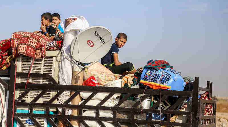 On 01 November children sit in the back of a truck loaded with their belongings on their way back home in Anbar Governorate, Iraq