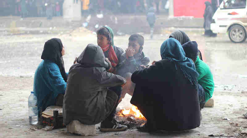 Children and their parents gather around a fire to keep warm in the yard of a large warehouse in Jibreen, now used as a shelter for thousands of families who fled violence in eastern Aleppo. Photo: UNICEF / UN043357 / Al-Issa