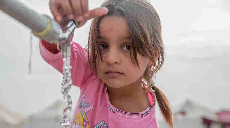 "A young girl from Mosul takes water from a tap stand at a UNICEF-supported Temporary Learning Space in Hassan Sham Displacement Camp, Ninewa Governorate. ""I like it here because we've been out of school for two years,"" she said. Photo: UNICEF"