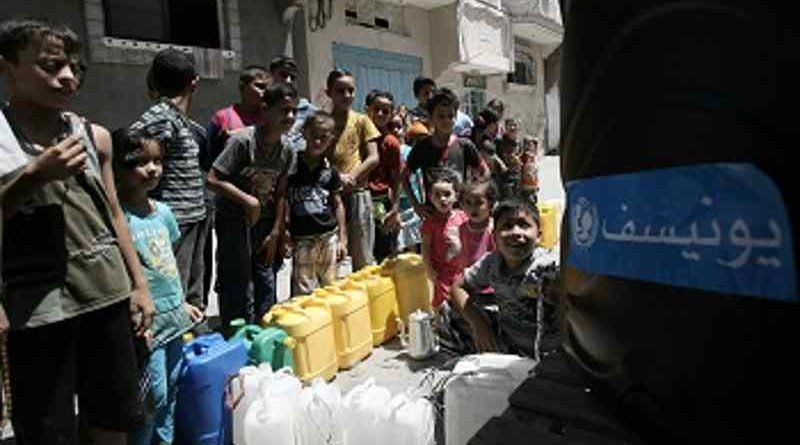 On 23 August 2014 children queue to fill jerrycans and other containers with water, at a filling station in Nuseirat, in the central Gaza Strip. Photo: UNICEF