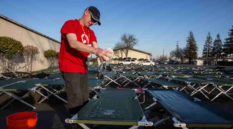 A Red Cross volunteer cleans cots outside of the Red Cross Silver Dollar Fairgrounds shelter in Chico, California.