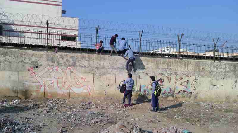 Students of a government school in Delhi cross high walls and barbed wires to abscond from the school. School education is bad and teachers have no control on students.