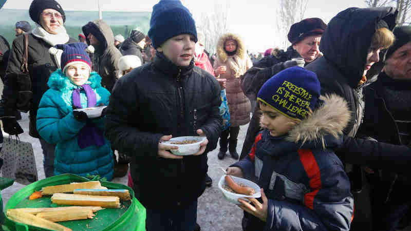 On 1 February 2017, children eat a hot meal at a heated emergency shelter in freezing cold Avdiivka, Ukraine, following intense fighting at the end of January 2017. Photo: UNICEF/Aleksey Filippov