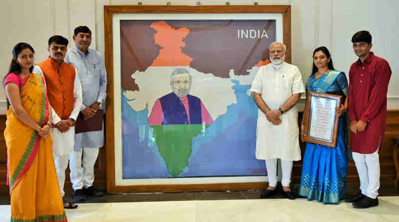Narendra Modi being presented the artwork made with pearls by artist Khushboo Akash Davda, in New Delhi on June 15, 2017