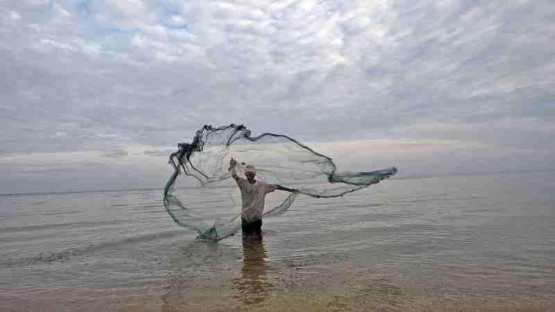 Fisherman in Timor Leste casts net in the water to catch small fish. UN Photo/Martine Perret