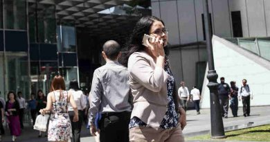 A woman speaks on the phone as she walks to work in Singapore. Photo: ILO/Giorgio Taraschi