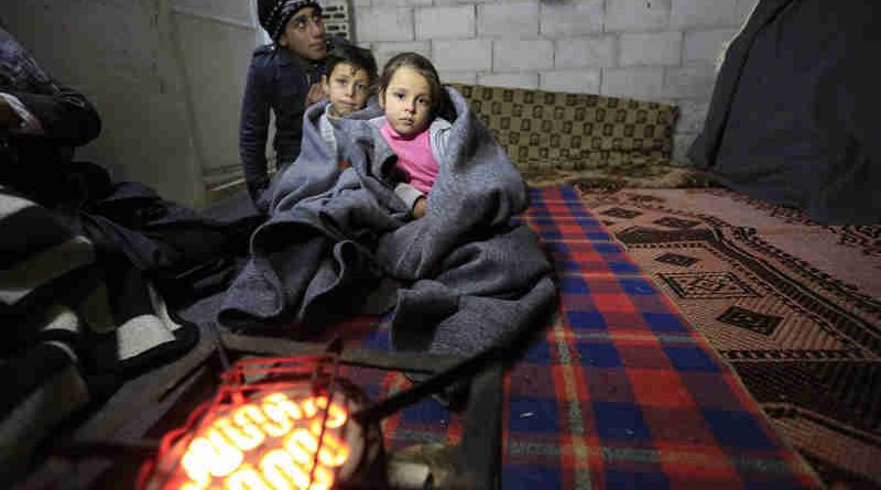 A Syrian family tries to keep warm in this unfinished building in the informal settlement of Al-Khalidia Al-Khamisa in Homs. UNICEF/Sanadiki (file)
