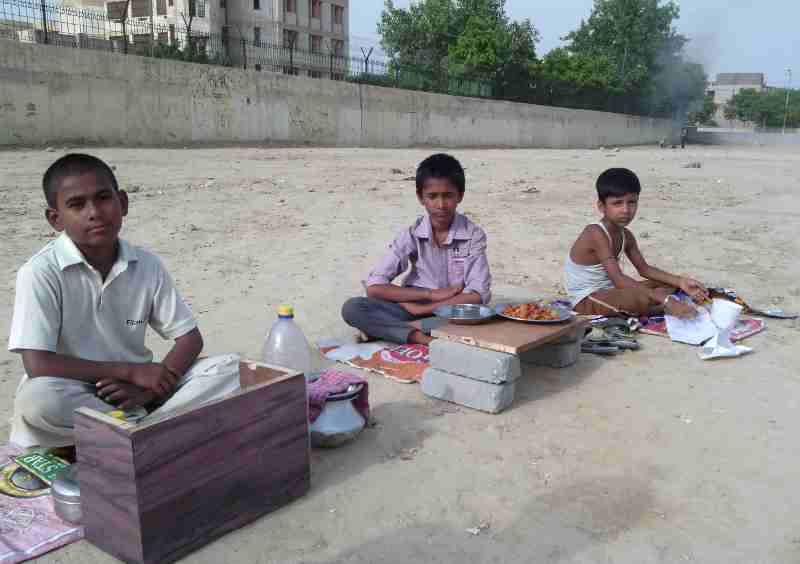 Young children forced by parents to sell eatables outside a school building in New Delhi, India. Click the photo to know the details.