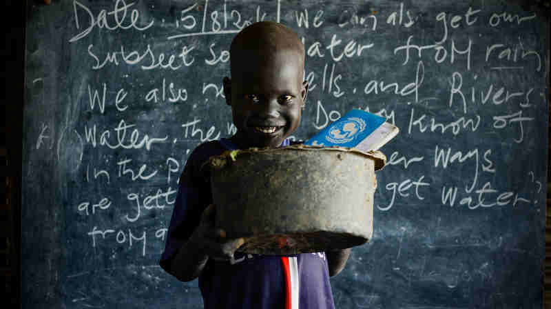 On 15 August 2016 in the Bentiu Protection of Civilians site (POC) in Unity State, Maet, 6, carries an old broken saucepan with a hole in it to school so he has something to sit on during class. Photo: UNICEF