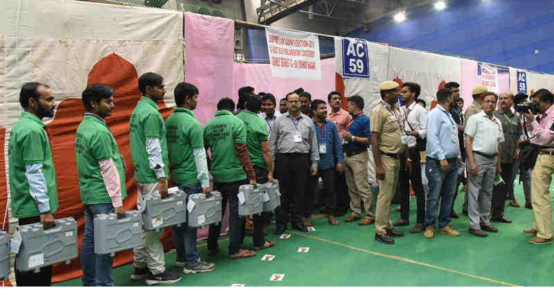 The Electoral Officials carrying Electronic Voting Machines (EVMs) for counting, at a Counting Centre of General Election-2019, at CWG Village, Sports Complex, in Delhi on May 23, 2019. Photo: PIB