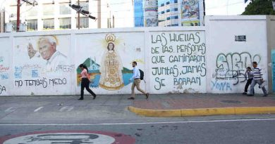 "3 June 2019: People pass in front of street graffiti in Caracas, Venezuela. The text reads: ""The footprints of those who travel together will never be erased."" Photo: UNICEF"