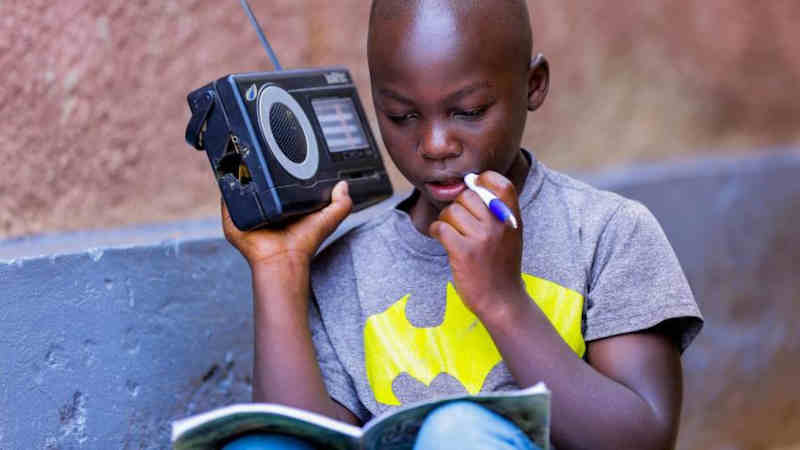 In Rwanda, a boy listens to a radio. Photo: UNICEF