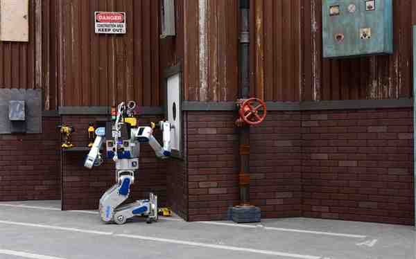 Team Kaist's robot DRC-Hubo uses a tool to cut a hole in a wall during the DARPA Robotics Challenge Finals, June 5-6, 2015, in Pomona, Calif. Team Kaist won the top prize at the competition. DARPA photo