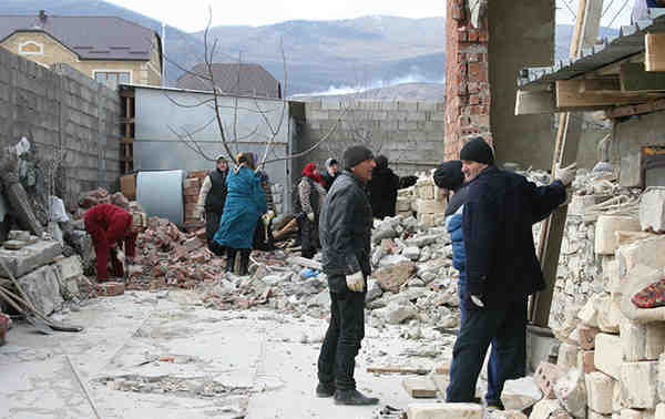 Local residents cleaning up the debris of a house destroyed in a counterinsurgency operation in Novyi Agachaul, Dagestan, February 2014.