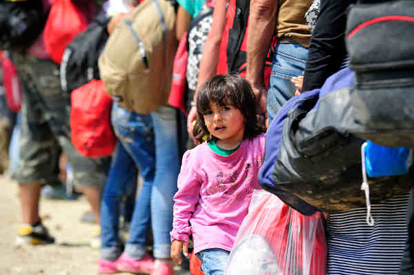 Near the town of Gevgelija, former Yugoslav Republic of Macedonia, a young Syrian girl holds the hand of an adult waiting to board a train to the Serbian border. Photo: UNICEF / Tomislav Georgiev
