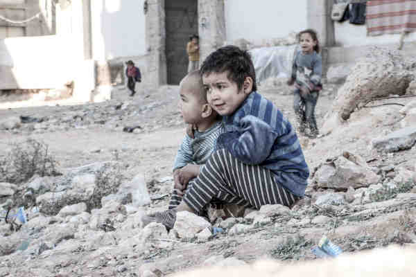 In Aleppo, Syria, four-year-old Esraa and her brother Waleed, three, sit on the ground near a shelter for internally displaced persons. Photo: UNICEF / Al-Issa