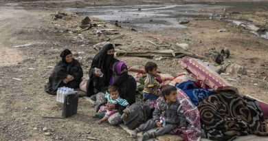 A family displaced by fighting in the village of Shora, 25 kilometres south of Mosul, wait by the roadside at an army checkpoint on the outskirts of Qayyarah. Photo: UNHCR / Ivor Prickett