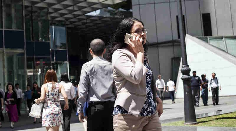 A woman speaks on the phone as she walks to work in Singapore. Photo: ILO/Giorgio Taraschi (Representational photo)