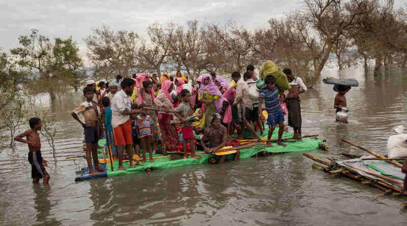 Rohingya refugees, including infants and children, on a makeshift raft made of logs, bamboo poles and jerrycans are brought to shore through the mangroves after they crossed the Naf River, which demarcates the border between Myanmar and Bangladesh, Sunday 12 November 2017. Photo: UNICEF