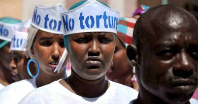 """Singers wearing hats advocating """"No Torture"""" line up before performing at a Human Rights Day event outside of Mogadishu Central Prison in Somalia. UN Photo/Tobin Jones"""
