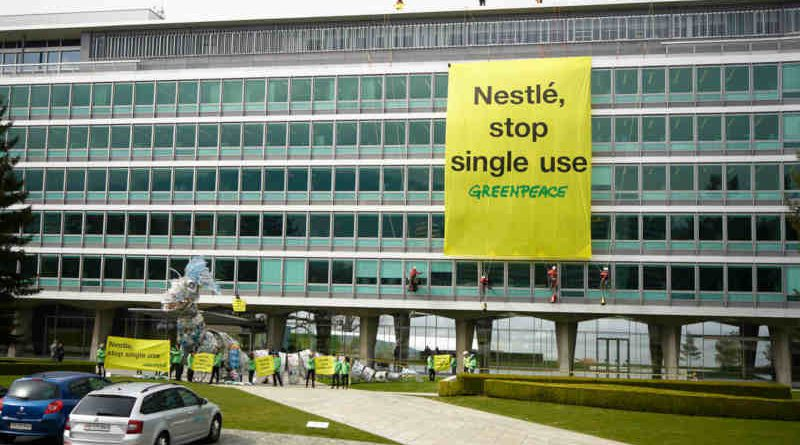 """Plastic Monster Action at Nestlé Headquarters in Switzerland. Greenpeace activists deliver a 20-meter-long """"plastic monster"""" covered in Nestlé branded plastic packaging to the company's global headquarters. Greenpeace is calling on Nestlé to end its reliance on single-use plastic. 16 April, 2019. Photo: Yukon Benner / Greenpeace"""