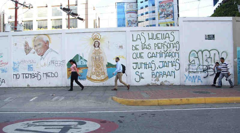 """3 June 2019: People pass in front of street graffiti in Caracas, Venezuela. The text reads: """"The footprints of those who travel together will never be erased."""" Photo: UNICEF"""