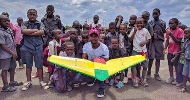 University student poses with school children at Kasungu Drone Corridor. A team of University of Malawi students, under the supervision of a team from Virginia Tech University, flew an autonomous 19 km simulated drug delivery flight in a drone. The drone was designed and built by the Malawian students. The flight testing occurred at the drone testing corridor in Kasungu. UNICEF through the Civil Aviation Authority (CAA) launched the air corridor to test potential humanitarian use of unmanned aerial vehicles (UAVs), also known as drones. The corridor is the first in Africa and one of the first globally. Drones have been used to test the feasibility of transporting laboratory samples for early infant HIV diagnosis, emergency medical supply delivery and vaccines. Photo: UNICEF